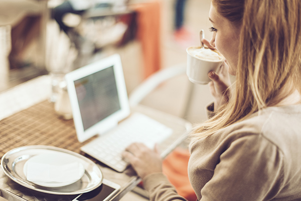 Woman online shopping with a laptop and cup of coffee