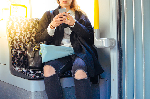 Midsection Of Woman Using Phone While Traveling In Train