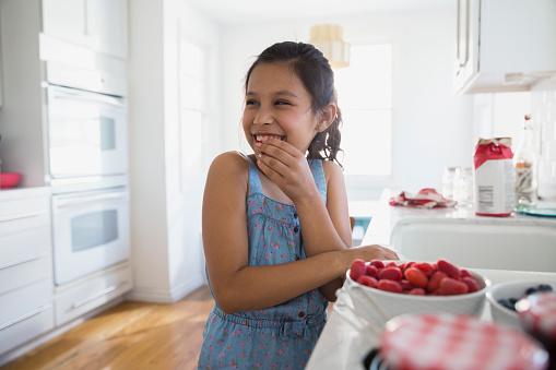 Smiling girl eating fresh berries in kitchen