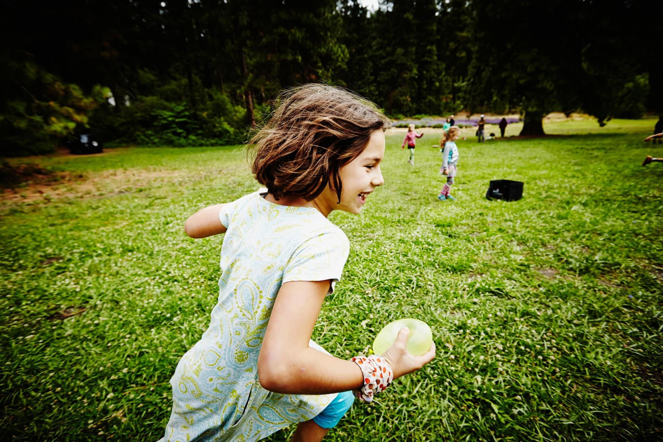 Little girl running and playing on grass